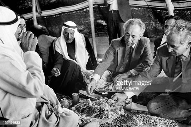 Israeli Prime Minister Shimon Peres enjoys a bedouin style meal under a traditional nomad's tant on January 29 1985 It is Peres first visit to this...