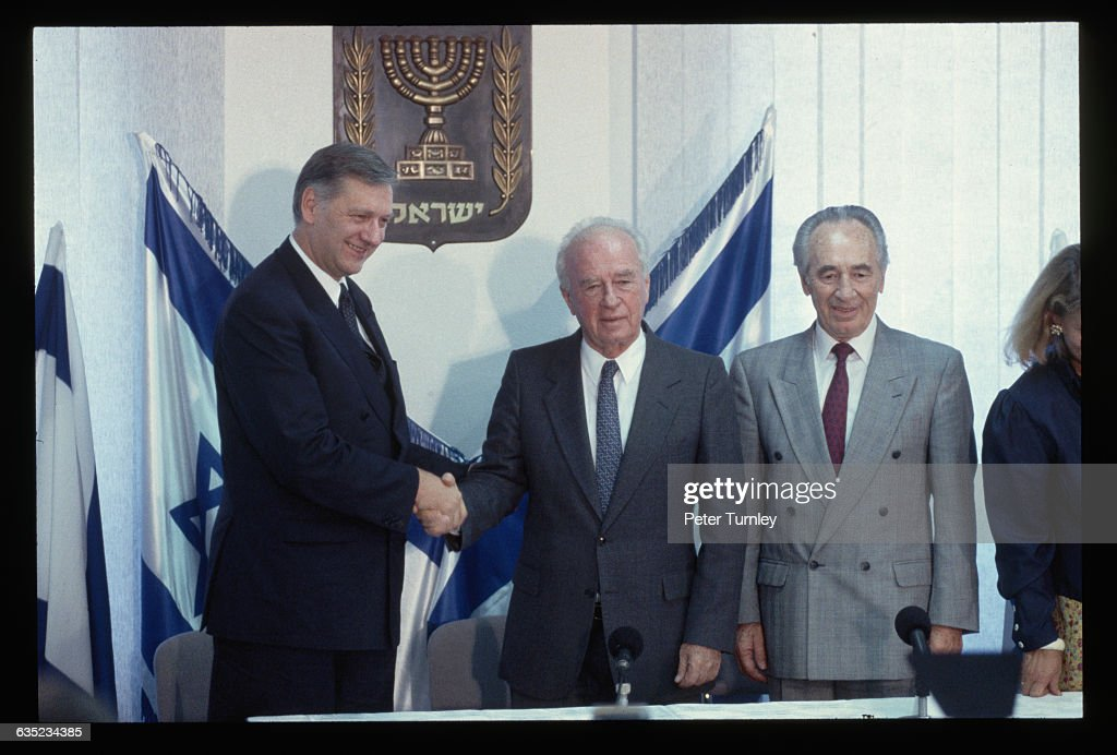 Israeli Prime Minister Yitzhak Rabin shakes hands with Norwegian Foreign Minister Johan Jorgen Holst at the signing of the peace agreement between Israel and the Palestine Liberation Organization (PLO). Rabin, Foreign Minister Shimon Peres (also shown), and PLO leader Yasser Arafat all went on to win the Nobel Peace Prize for signing the agreement.