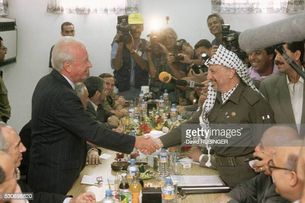 Israeli Prime Minister Yitzhak Rabin shakes Palestinian Authority President Yasser Arafat's hand at the Erez Checkpoint, on the border of the Gaza...