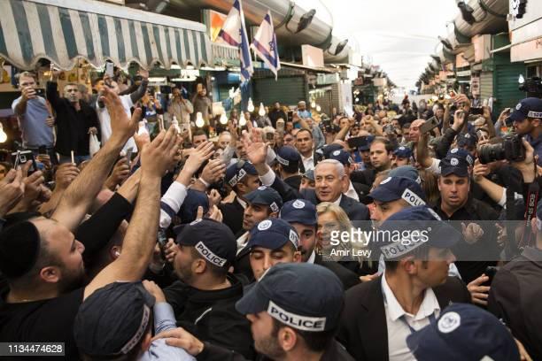 Israeli Prime Minster Benjamin Netanyahu and his wife Sara Netanyahu gesture to supporters as they visit Tel Aviv's vegetable market Hatikva on April...