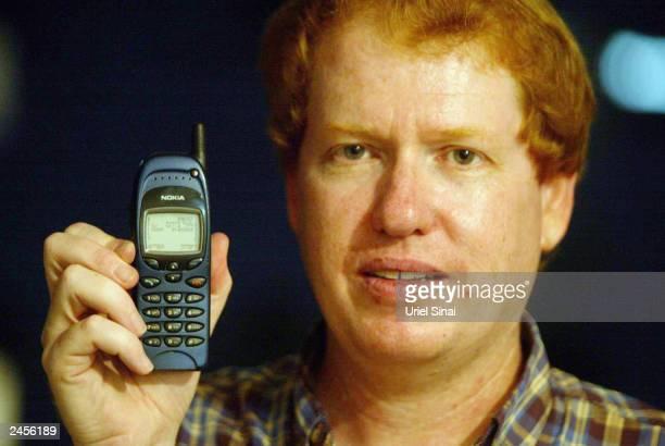 Israeli Professor Eli Biham holds a Nokia GSM phone September 2 2003 in Holon Israel Professor Eli Biham and his doctoral assistant Elad Barkan both...