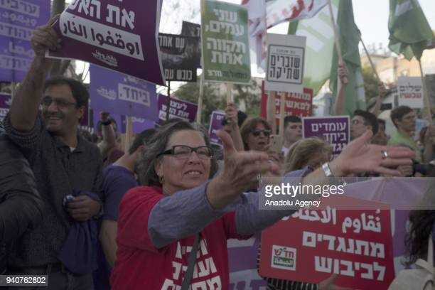 Israeli protesters hold placards during a demonstration against Israel's attitude to Palestinians at GazaIsrael border demanding a political solution...