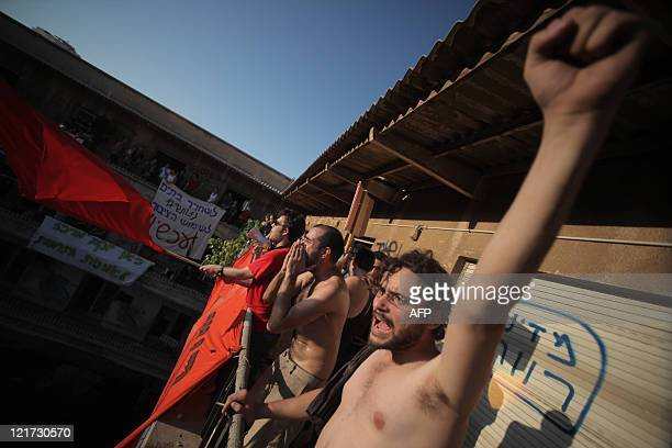 Israeli protesters stand on the balcony of an abandoned building in Tel Aviv on August 22, 2011 after entering the premesis by force in protest...