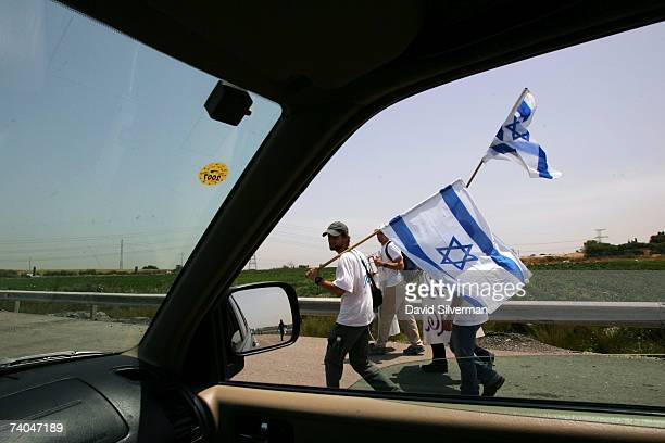 Israeli protestors march along the highway, displaying national flags and signs calling for the resignation of Prime Minister Ehud Olmert, during a...