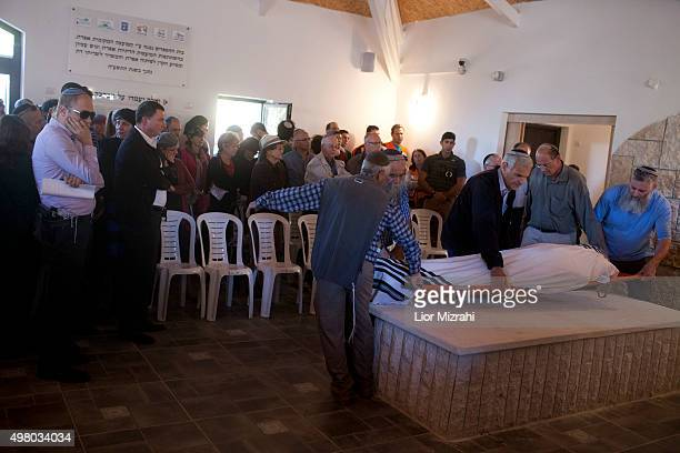 Israeli relatives of Ya'akov Don cry next to the body draped in a prayer shawl during funeral services on November 20, 2015 in the Jewish settlement...
