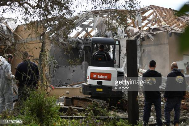 Israeli rescue team inspect the scene of a house that was hit by a rocket fired from the Gaza Strip in Moshav Mishmeret central Israel causing the...