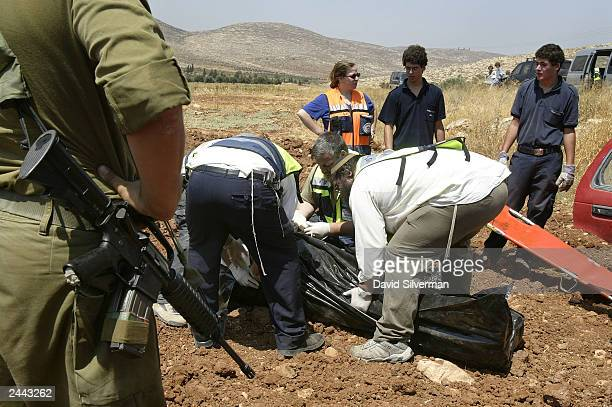 Israeli rescue workers tend to the body of a Jewish settler shortly after was killed August 29, 2003 during a Palestinian shooting attack near the...