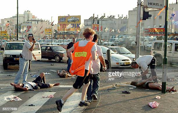 Israeli rescue workers tend to wounded people at the site of a suicide attack in Netanya 12 July 2005 At least two Israelis were killed and around 40...