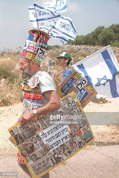 Israeli rightwing militant Shmuel Bani covered with antigovernment and peace stickers marches among a thousand of Jewish settlers marking the Jewish...