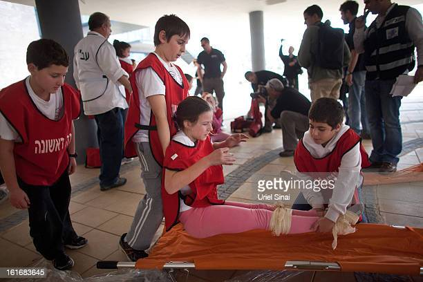 Israeli schoolchildren act as the wounded during a Home Front command drill simulating a rocket hitting a school on February 14, 2013 in Ra'anana,...