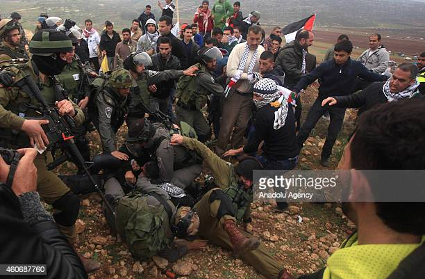 Israeli security detains a demonstrator and others try to set free him during a protest against separation barrier after Friday Prayer in Turmusayye...