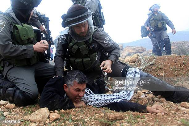 Israeli security detains a Palestinian man during a protest against separation barrier after Friday Prayer in Turmusayye town where Palestinian...