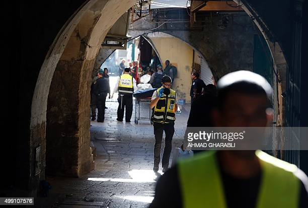 Israeli security forces and emergency personnel carry on a stretcher the covered body of a Palestinian man who stabbed and seriously wounded an...