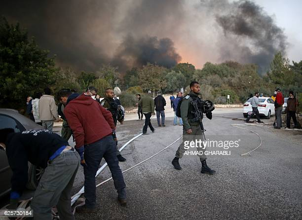 Israeli security forces and volunteers help firefighters battle to control a fire that broke out in the Israeli town of Nataf west of the Arab...