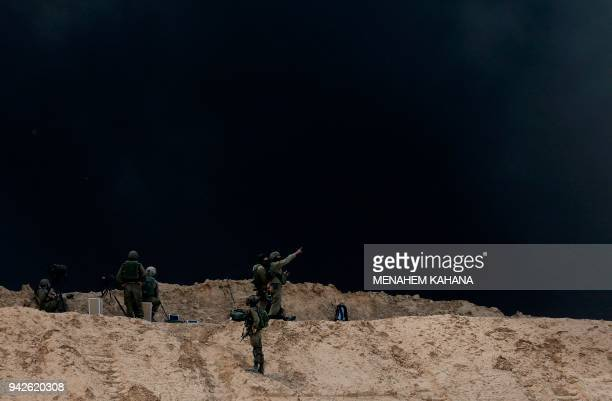 TOPSHOT Israeli security forces are deployed near Kibbutz Nir Oz on the Israeli border with the southern Gaza Strip as smoke billows from tyres...