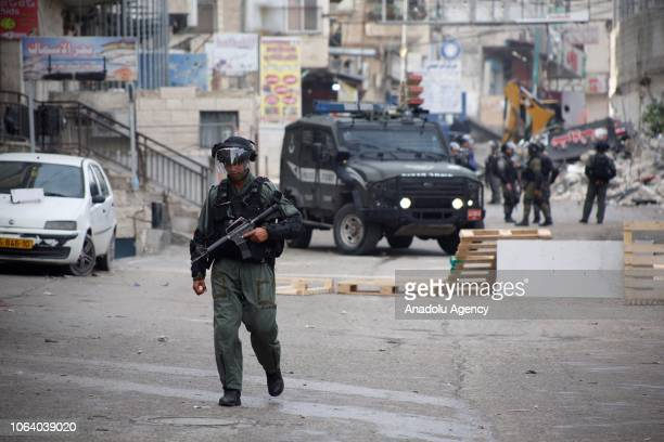 Israeli security forces are seen as an excavator demolishes shops that belong to Palestinians at Ras Hamees neighborhood near Shuafat refugee camp in...