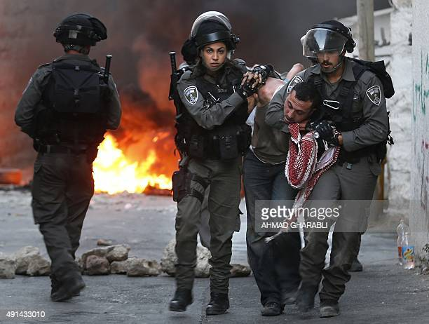 Israeli security forces arrest a Palestinian during clashes in the Palestinian neighborhood of Shuafat in east Jerusalem on October 5 2015 as...