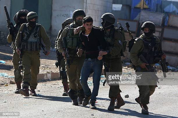 Israeli security forces arrest a Palestinian man during clashes in Qabatiya a town near Jenin in the north of the Israelioccupied West Bank on...