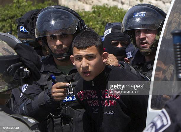 Israeli security forces arrest a Palestinian youth during clashes in the east Jerusalem neighbourhood of Ras alAmud on April 18 2014 following Friday...