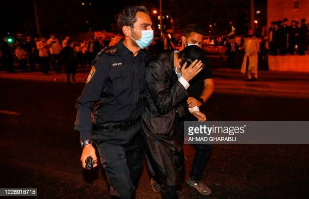 Israeli security forces arrest an UltraOrthodox Jewish man during a protest against the enforcement of coronavirus emergency regulations in the Ultra...