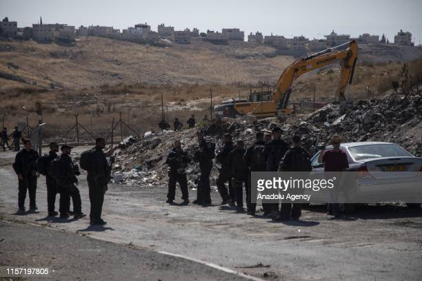 Israeli security forces block the roads that reach the buildings which are being demolished with bulldozers under Israeli soldiers supervision as...