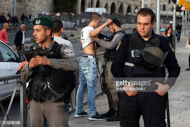 Israeli security forces bodycheck a Palestinian young man at the entrance of Damascus Gate outside Jerusalem's Old City on March 9 2016 / AFP / AHMAD...