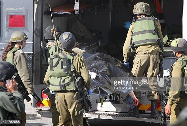 Israeli security forces carry the body of a Palestinian man who stabbed and lightly wounded an Israeli border guard before being shot dead by another...