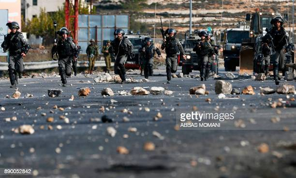 TOPSHOT Israeli security forces clash with Palestinian protestors in the West Bank city of Ramallah on December 11 2017 as demonstrations continue to...