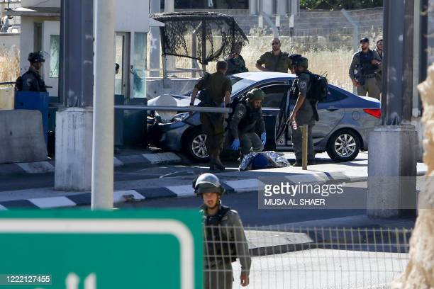 Israeli security forces cover the body of Palestinian Ahmad Erakat, who was shot dead at the site of a reported ramming attack, at a checkpoint in...
