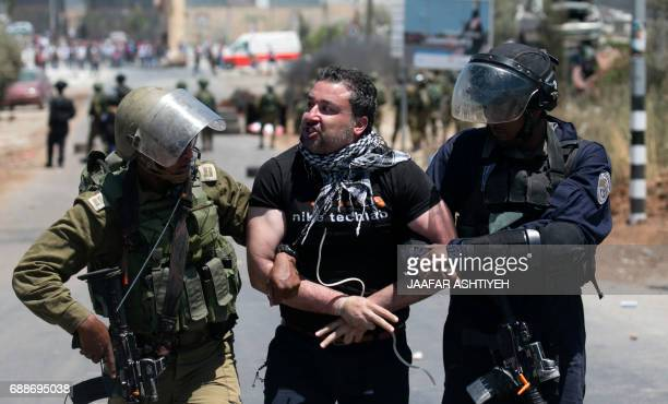 Israeli security forces detain a Palestinian demonstrator during clashes following a Friday noon prayer in solidarity with Palestinian prisoners held...