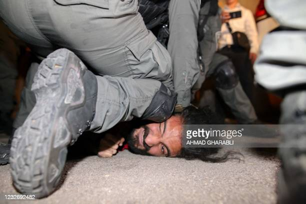 Israeli security forces detain a Palestinian man amid ongoing confrontations as Palestinian families face eviction in the Sheikh Jarrah neighbourhood...