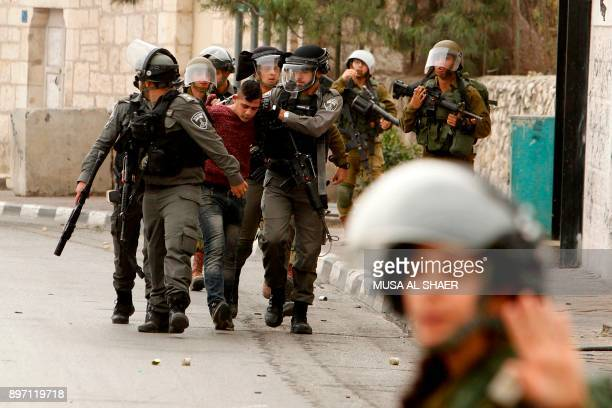 TOPSHOT Israeli security forces detain a Palestinian protester during clashes at the main entrance of the Israeli occupied West Bank city of...