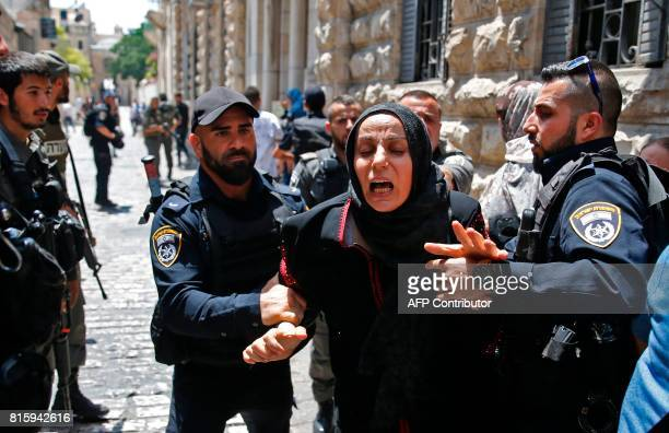 Israeli security forces detain a Palestinian woman during a demonstration outside the Lions Gate a main entrance to AlAqsa mosque compound due to...
