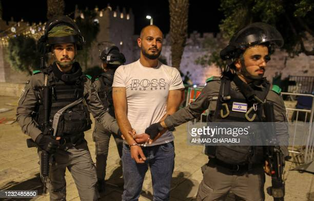Israeli security forces detain a protester during clashes with Palestinian protesters outside the Damascus Gate in Jerusalem's Old City on April 23...