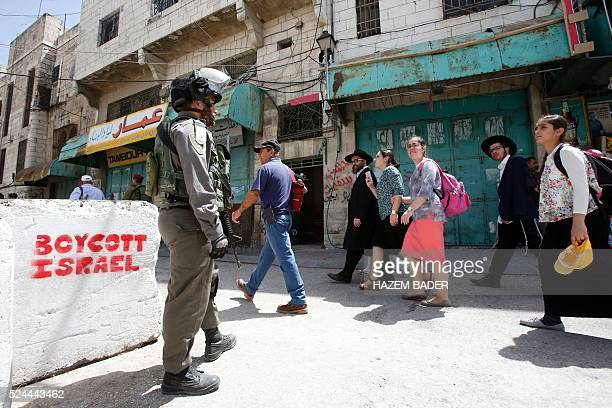 Israeli security forces escort a group of Jewish settlers through a Palestinian neighbourhood in the divided West Bank city of Hebron as they are...