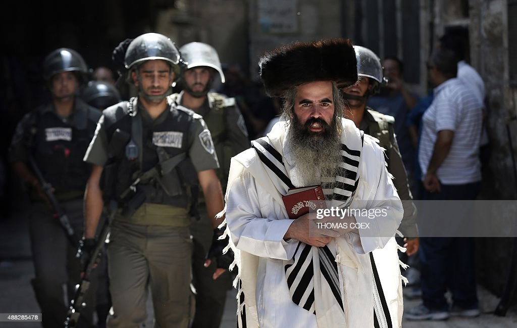 Israeli security forces escort Jewish worshippers coming from the Western Wall, Judaism's holiest site, as they cross the Muslim quarter in Jerusalem's Old City on September 15, 2015 during scuffles between Palestinian Muslims and Israeli security forces. Muslims and Israeli police clashed at Jerusalem's flashpoint Al-Aqsa mosque compound for a third straight day as Jews celebrated their new year and protesters vowed to protect Islam's third-holiest site.