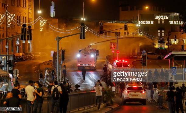 Israeli security forces fire a water cannon during clashes with Palestinian protesters outside the Damascus Gate in Jerusalem's Old City on May 9,...