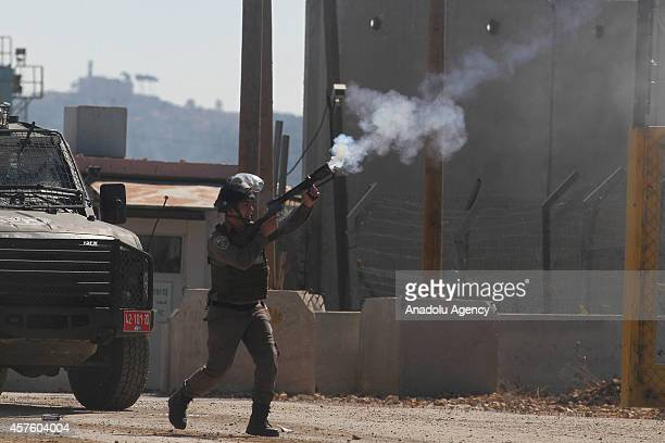 Israeli security forces fire smoke grenade at Palestinian protesters during clashes at the entrance of the Israeli Ofer military prison in Ramallah...