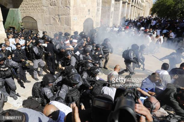 Israeli security forces fire sound grenades inside the AlAqsa Mosque compound in the Old City of Jerusalem on August 11 as clashes broke out during...