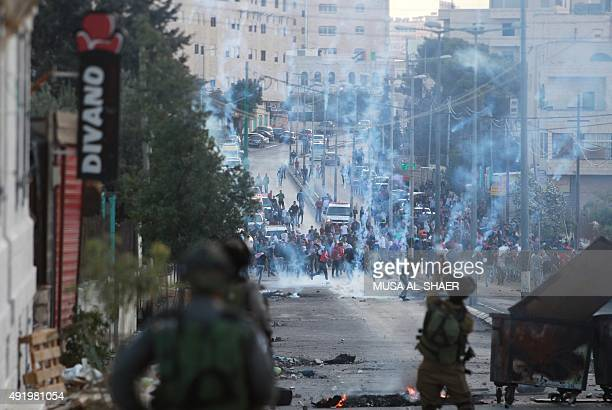 Israeli security forces fire tear gas grenades towards Palestinian demonstraters during clashes in the West Bank town of Bethlehem on October 9 2015...