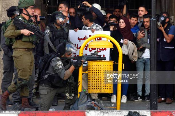 TOPSHOT Israeli security forces fire tear gas towards Palestinian demonstrators on November 26 2019 during clashes in the West Bank city of Hebron...