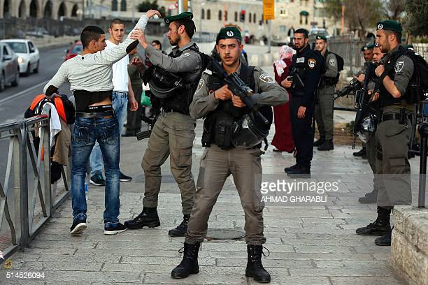 Israeli security forces frisk a Palestinian young man at the entrance of Damascus Gate outside Jerusalem's Old City on March 9 2016 / AFP / AHMAD...
