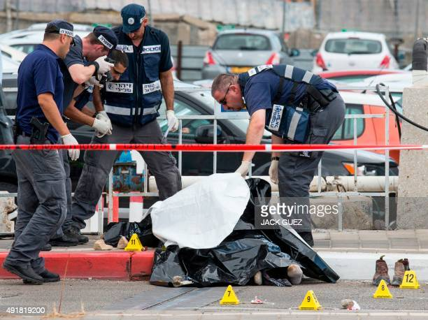 Israeli security forces inspect the body of a Palestinian man who was shot dead after carrying out a stabbing attack on an Israeli soldier and three...