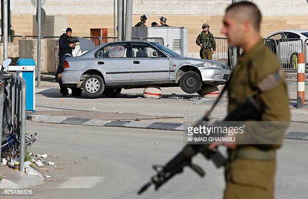 Israeli security forces inspect the car of a Palestinian woman who they say drove her vehicle towards Israeli guards at the Qalandia checkpoint...