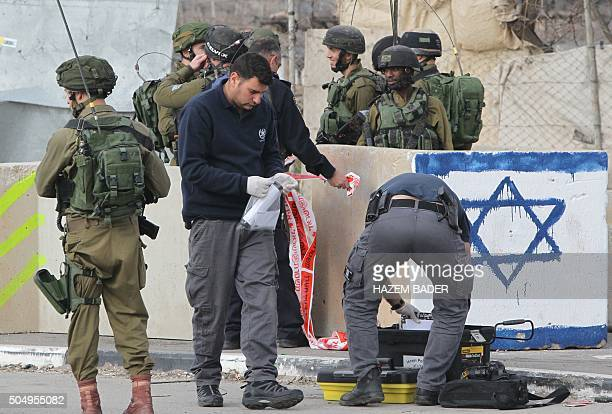 Israeli security forces inspect the scene where a Palestinian was shot dead after attempting to stab Israeli soldiers at the Beit Einun junction...