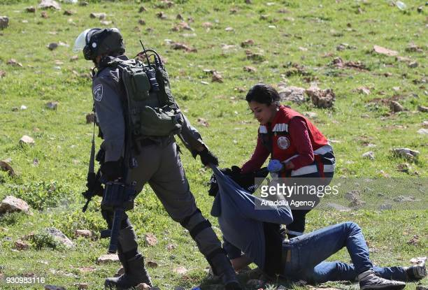 Israeli security forces intervene Palestinian medical staff as they try to move away a wounded man during a protest in Ramallah West Bank on March 12...
