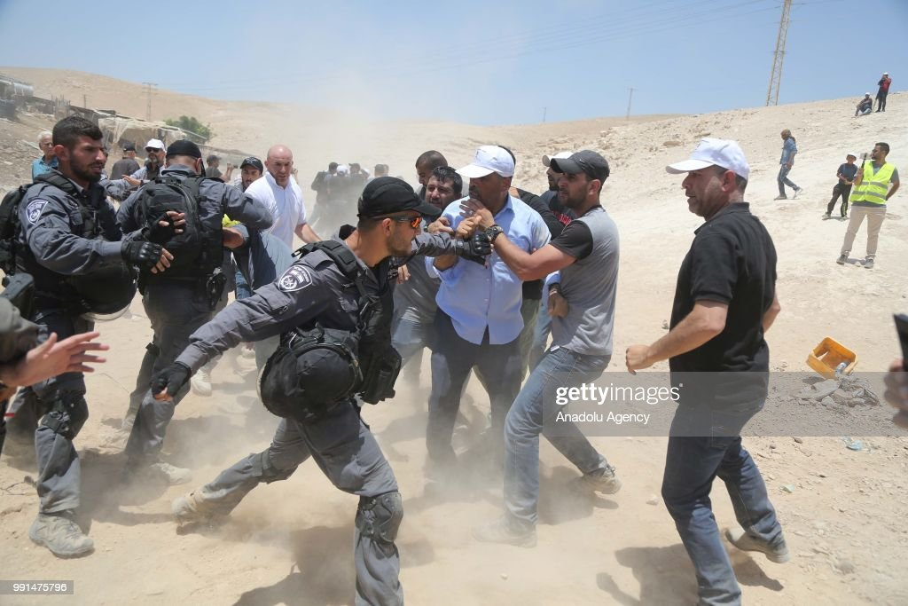 Israeli security forces intervene Palestinians as Palestinians try to prevent them to destroy their tents and sheds with bulldozers in Khan al-Ahmar village of eastern Jerusalem on July 04, 2018.