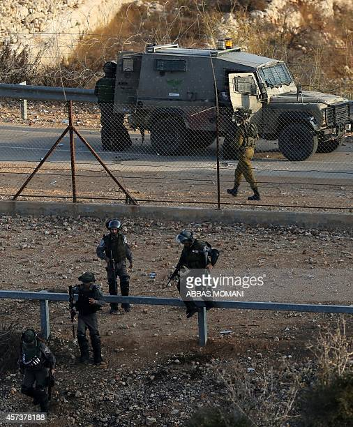 Israeli security forces jump over a fence during clashes with Palestinian protesters close to the Israeli Ofer military prison near the West Bank...