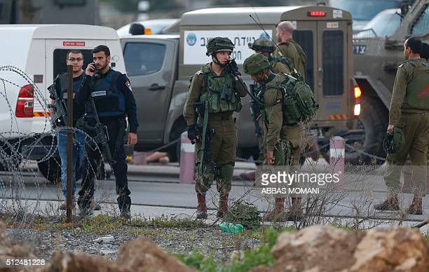 Israeli security forces monitor the area where a Palestinian man tried to stab Israeli soldiers before being shot dead at a checkpoint near Ramallah...