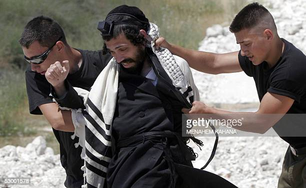 Israeli security forces push away an ultraorthodox Jew wearing prayer shawl and a phylacteries during a demonstration against the desecration of...